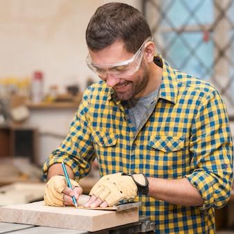 Primo piano delle mani dell'artigiano in guanti protettivi che misurano blocco di legno con il righello e la matita