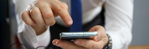 Primo piano delle mani dell'uomo d'affari facendo uso dello smartphone moderno. documenti e rapporti commerciali sul desktop. impiegato che manda un sms con il dito tramite telefono cellulare. concetto di finanza ed economia