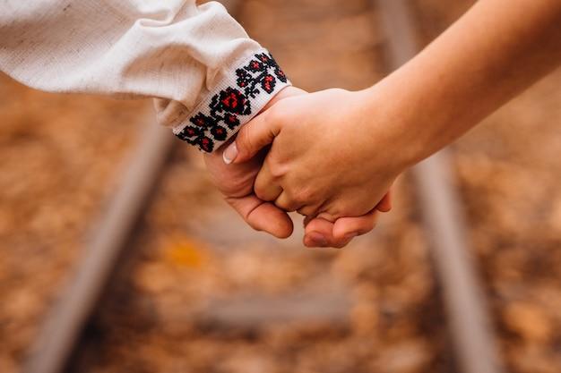 Primo piano delle mani della coppia tenute insieme sopra le rotaie