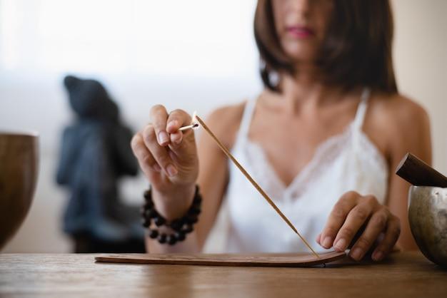 Primo piano delle mani della donna che brucia un bastoncino di incenso nel suo salotto. donna che medita in atmosfera buddista durante l'isolamento a casa.