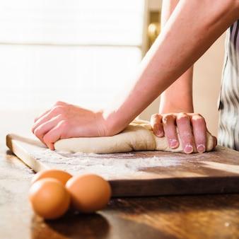 Primo piano delle mani della donna che impasta la pasta sul tagliere con tre uova sulla tavola di legno
