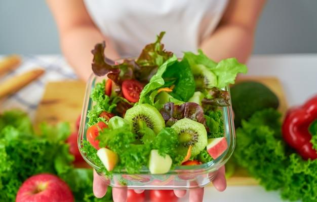 Primo piano delle mani della donna che mostrano l'insalatiera e le varie verdure a foglia verde sulla tavola a casa.