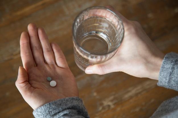 Primo piano delle mani della donna che tengono bicchiere d'acqua e pillole