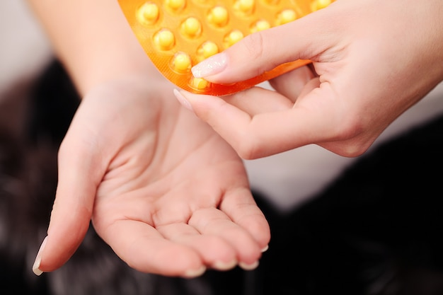 Primo piano delle mani della donna che tengono le pillole della medicina