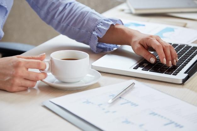 Primo piano delle mani della donna di affari che digitano sul computer portatile e che tengono una tazza di tè