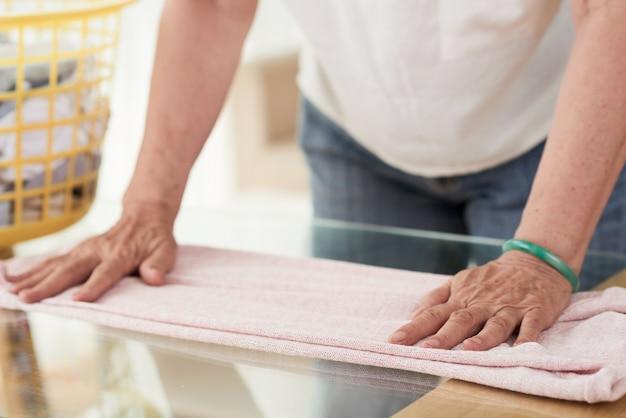 Primo piano delle mani della donna irriconoscibile che piega i vestiti asciutti