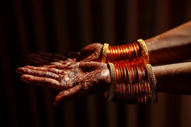 Primo piano delle mani della sposa indù coperto con tatuaggi all'hennè