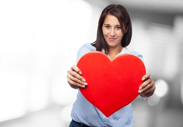 Primo piano delle mani di affari che tiene un cuore rosso