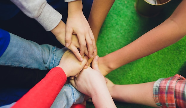 Primo piano delle mani di molti bambini che tengono insieme come una squadra sulla natura.