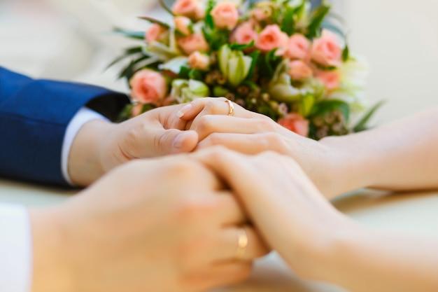Primo piano delle mani di nozze con anelli