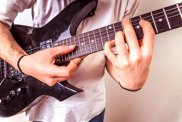 Primo piano delle mani di un chitarrista che esegue una canzone mentre preme le corde.