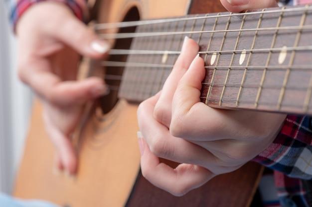 Primo piano delle mani di una giovane donna a suonare la chitarra