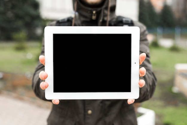 Primo piano delle mani di una persona che mostrano schermo in bianco della compressa digitale