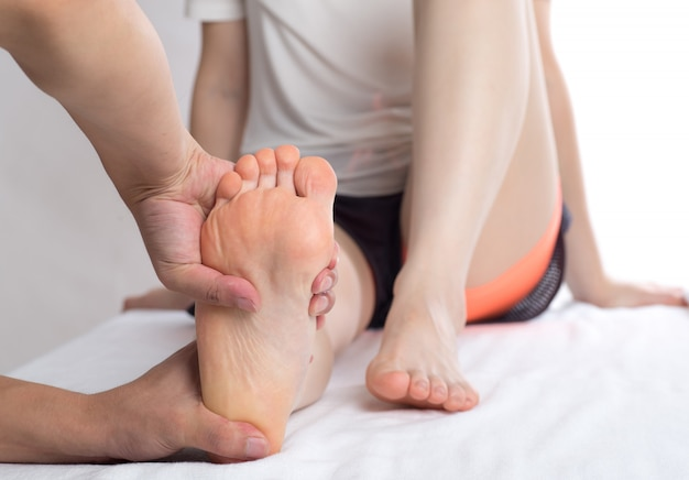 Primo piano delle mani femminili che fanno massaggio ai piedi