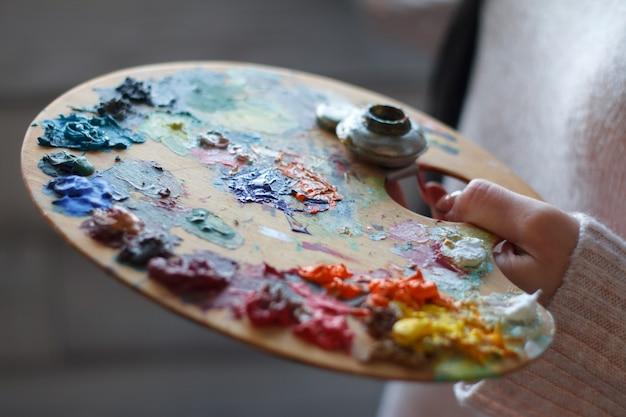 Primo piano delle mani femminili che mescolano le vernici su una gamma di colori