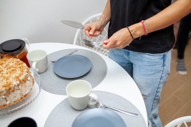 Primo piano delle mani femminili che tengono la spatola e la forcella del dolce. sul tavolo c'è una torta, piatti e tazze. tea party fatto in casa