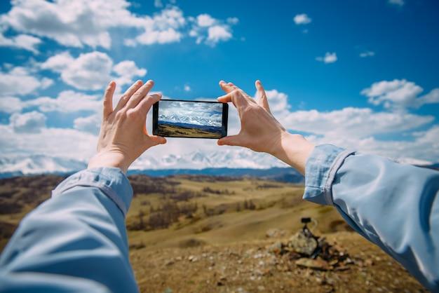 Primo piano delle mani femminili che tengono smartphone e che prendono foto o video.