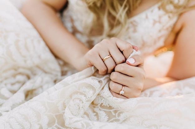 Primo piano delle mani femminili con il matrimonio e gli anelli di fidanzamento.