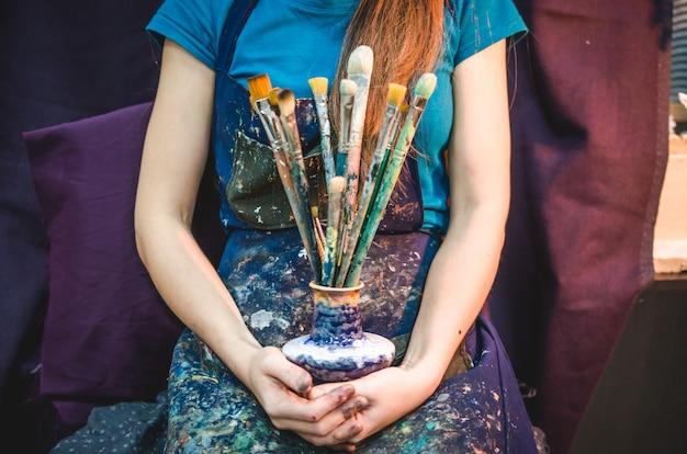 Primo piano delle mani femminili dell'artista con i pennelli