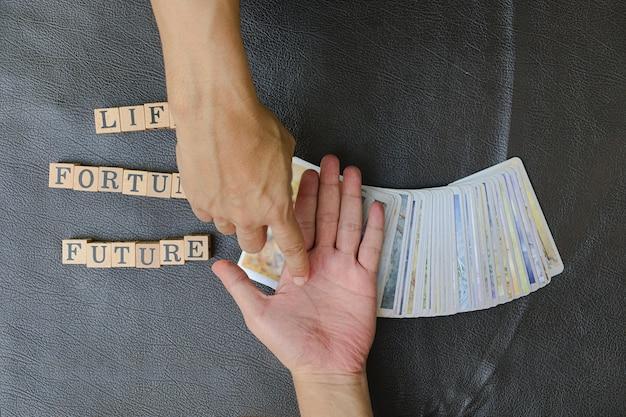 Primo piano delle mani giuste dell'indovino che indicano l'impronta digitale delle persone sulle previsioni sul destino futuro