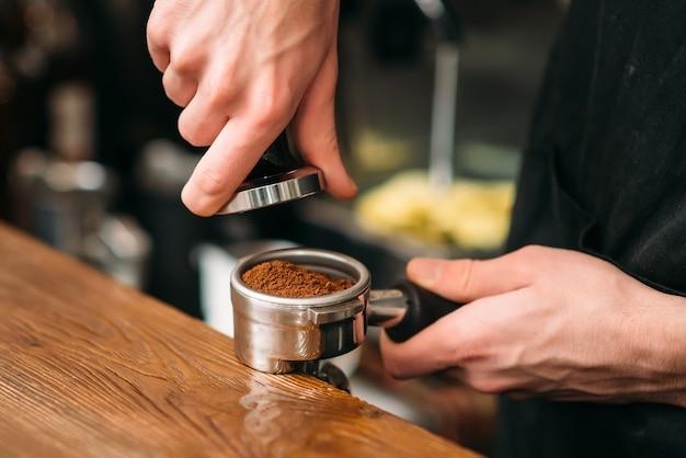 Primo piano delle mani maschii che cucinano caffè.
