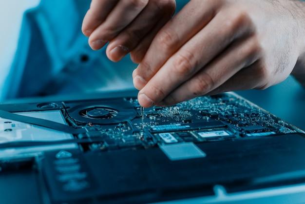 Primo piano delle mani maschii che riparano computer portatile. hardware.