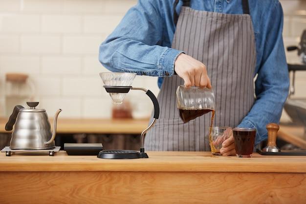 Primo piano delle mani maschii di barista che versano caffè alternativo dal chemex.