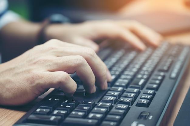 Primo piano delle mani maschii digitanti sulla tastiera.