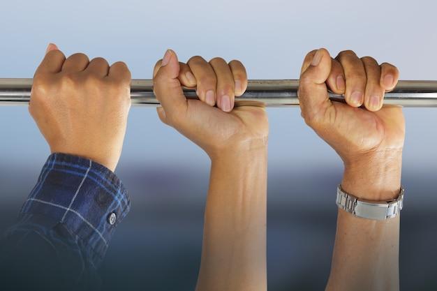 Primo piano delle mani maschii nella barra orizzontale