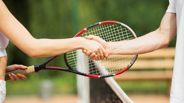 Primo piano delle mani stringere delle coppie di tennis