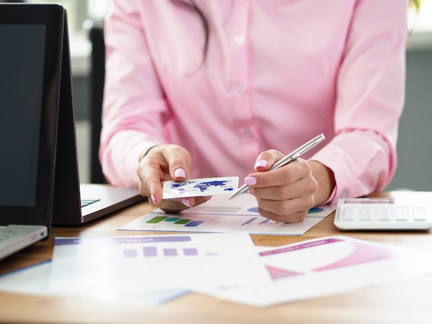 Primo piano delle mani tenere della donna di affari che tengono la carta e la penna di credito. imprenditrice compilando documenti finanziari. concetto di servizi bancari e aziendali