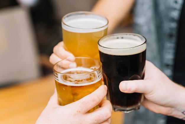 Primo piano delle mani tifo per i bicchieri di birra