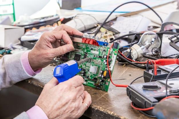 Primo piano delle mani uomini tenere strumento riparazione elettronica produzione servizi, assemblaggio manuale di circuiti di saldatura.