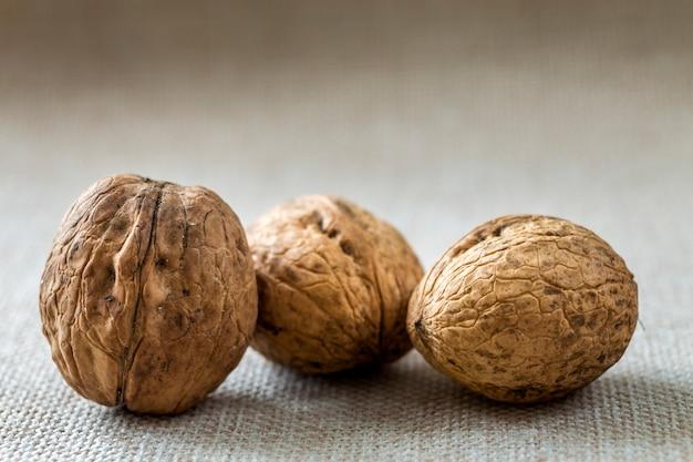 Primo piano delle noci nelle coperture di legno isolate su luce concetto saporito sano dell'alimento biologico.
