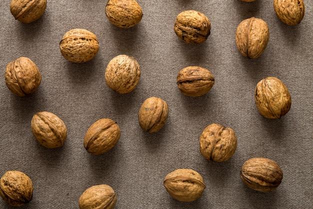 Primo piano delle noci nelle coperture di legno isolate sul fondo leggero dello spazio della copia, vista superiore. concetto sano gustoso cibo biologico.