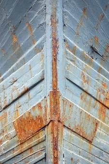 Primo piano delle pareti arrugginite della nave del ferro con pittura grigia su