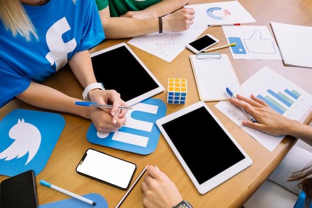 Primo piano delle persone di affari con le icone digitali di media e della compressa digitale sul tavolo