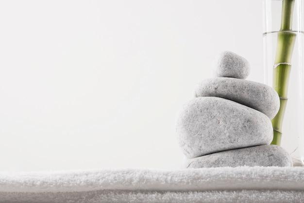 Primo piano delle pietre di zen e pianta di bambù in vaso sull'asciugamano bianco isolato su fondo bianco