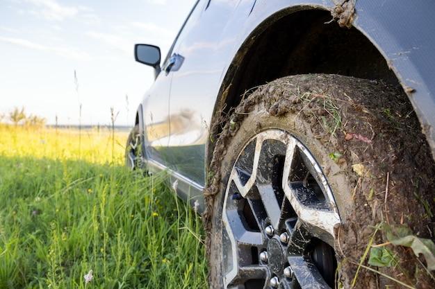 Primo piano delle ruote di automobile fuori strada sporche con le gomme sporche