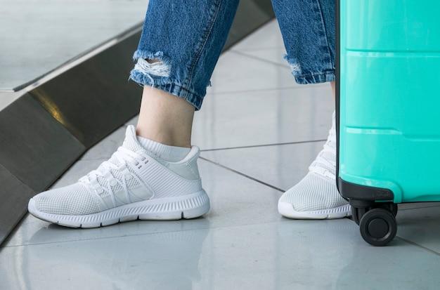 Primo piano delle scarpe bianche della donna in aeroporto