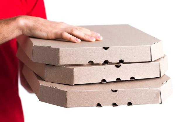Primo piano delle scatole della tenuta del ragazzo della pizza di consegna