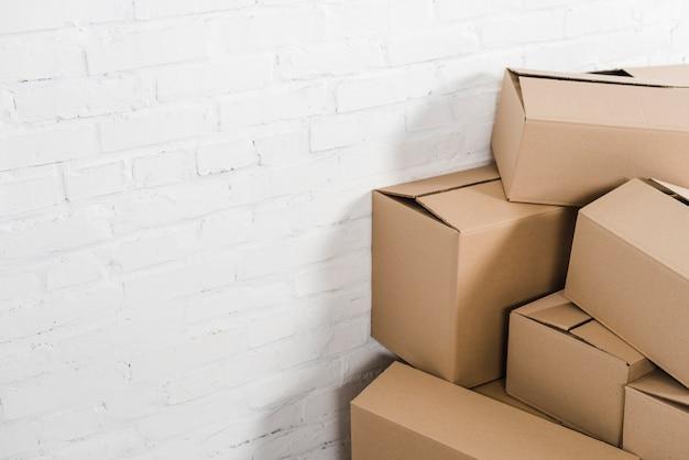 Primo piano delle scatole di cartone davanti al muro di mattoni bianco