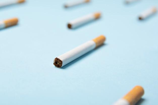 Primo piano delle sigarette del tabacco su pastello blu