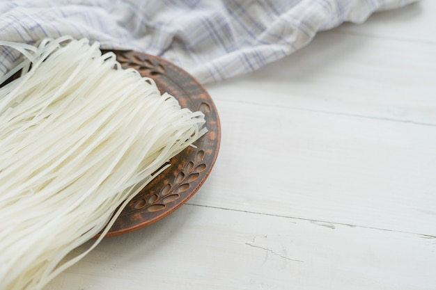 Primo piano delle tagliatelle dei vermicelli del riso sul piatto rotondo con la tovaglia sopra fondo bianco