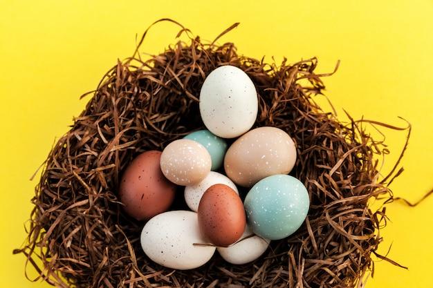 Primo piano delle uova di pasqua nel nido su superficie gialla, celebrazione della molla