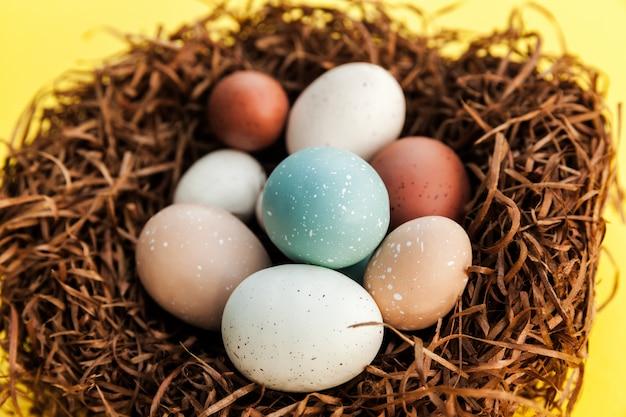 Primo piano delle uova di pasqua nel nido su superficie gialla, decorazione tradizionale