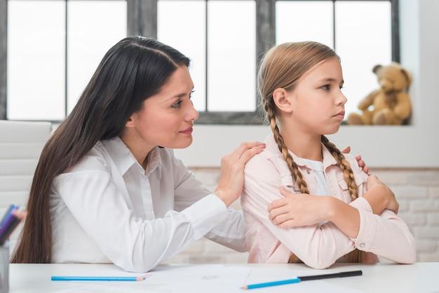 Primo piano dello psicologo femminile che conforta la sua bambina depressa