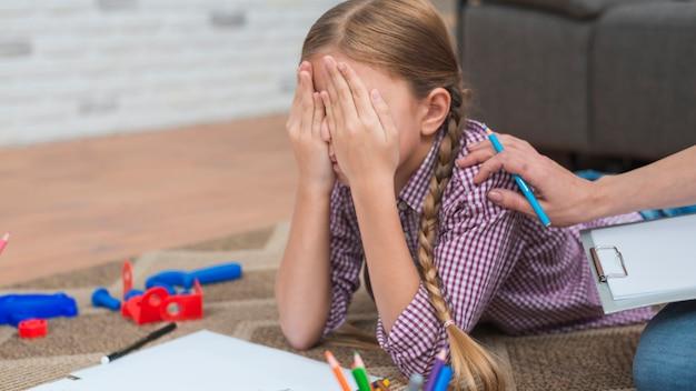 Primo piano dello psicologo femminile che consola la ragazza depressa che copre il suo fronte di mani