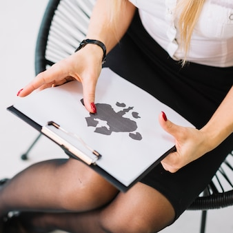 Primo piano dello psicologo femminile che tiene la carta reattiva del inkblot del rorschach sulla lavagna per appunti