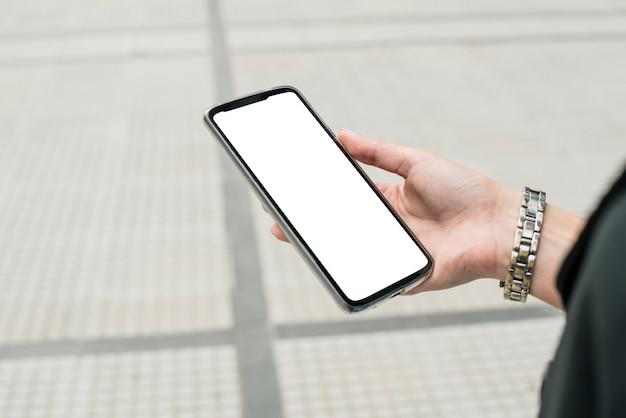 Primo piano dello smartphone della holding della mano della donna di affari che video schermo bianco